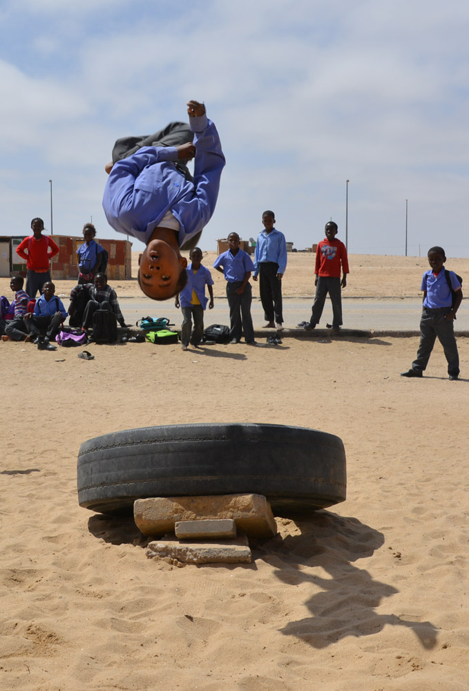 Local children in Namibia passing the time practicing their acrobatic skills.