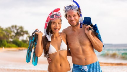 Healthy lifestyle fit body beach snorkel couple with diving masks and fins. Bikini swim models in swimwear snorkeling equipment. Asian girl, caucasian man on summer travel vacations, active lifestyle.